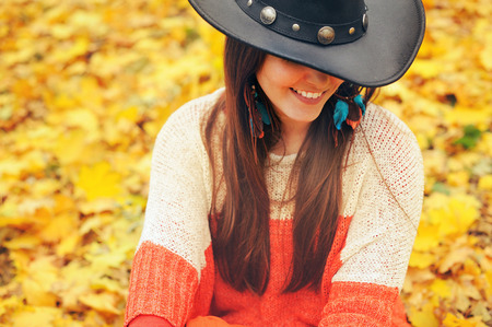hair part: Fashion smiling woman dressed in boho chic style hat,  take a rest in autumn park, part of face, perfect teeth, autumn leaves backdrop Stock Photo