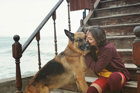 shepherd's companion: Happy woman kissing her German shepherd dog on a stairs against sea, outdoor