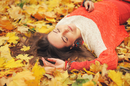 Smiling happy girl portrait, lying in autumn leaves, relax with closed eyes, dressed in fashion sweater, autumn outdoor photo