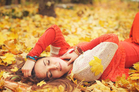 Happy resting girl portrait, lying in autumn maple leaves in park, closed eyes, dressed in fashion sweater and many friendship bracelets, outdoor photo