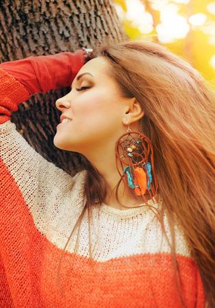 Smiling happy girl profile beauty portrait, fashion boho chic style dreamcatcher earrings, autumn outdoor, soft vintfge colors photo