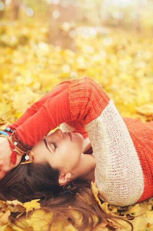 Calm relaxed woman profile portrait, take a rest lying in autumn  leaves in park, closed eyes, many bracelets on hands, outdoor photo