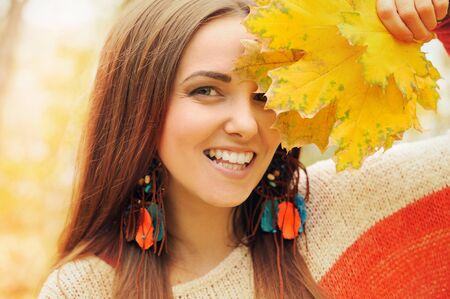 Beautiful smiling woman outdoor portrait, fresh skin and healthy smile, hold maple leaves bunch front of face, dressed in fashion leather earrings photo