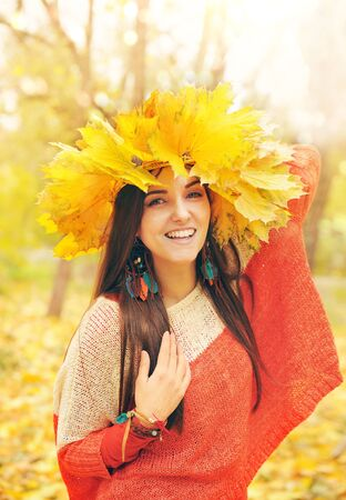 Beautiful smiling woman with wreath of maple leaves on a head, bright sunny outdoor portrait photo