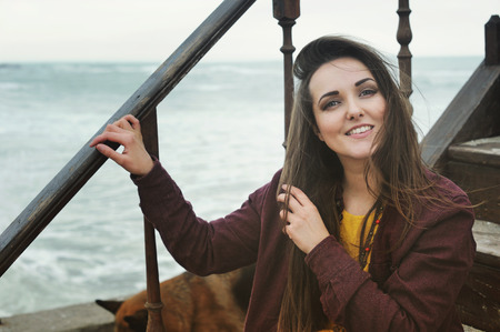 Beautiful smiling brunette girl sitting on a stairs against seascape, smiling and looking at camera. Fresh skin and healthy smile photo