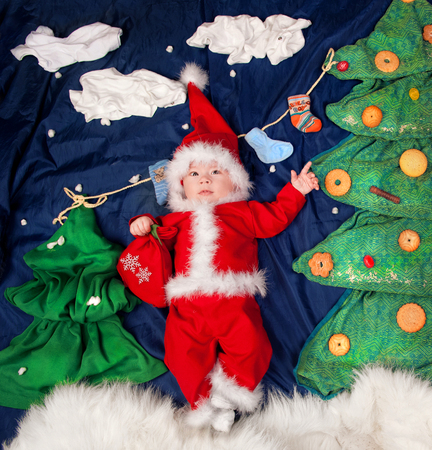 Infant baby boy wearing Santa costume holding bag with gifts. Posing against textile decoration of a christmas trees decorated cookies and sweets Stock Photo