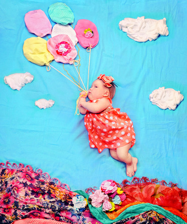 Infant baby girl flying on a helium balloons, against textile decoration of a floral meadow and blue sky