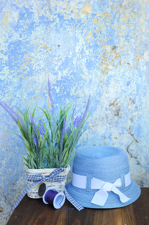 Blue sun hat and lavender flowers against old cracked wall in Greece, copy space for text, touristic concept