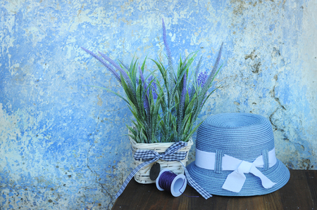 Sun hat and lavender flowers against old blue cracked wall in Greece, touristic concept, empty space for text