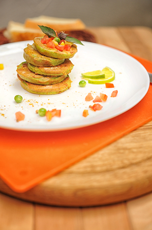 Vegetable fritters of zucchini on a wooden table Stock Photo