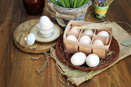 Close-up view of organic raw chicken eggs in egg box on old dark wooden background