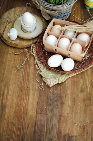 Organic raw chicken eggs in egg box on wooden background with place for text Stock Photo