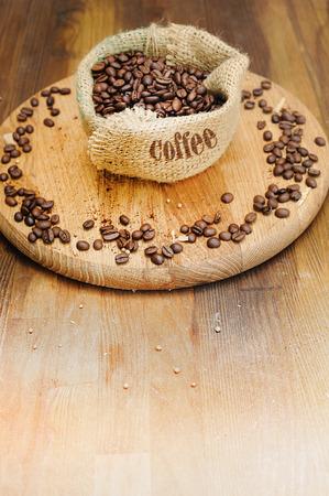 コーヒー豆とコピーのテキストのための領域で、古い木製の背景の上に袋バッグ