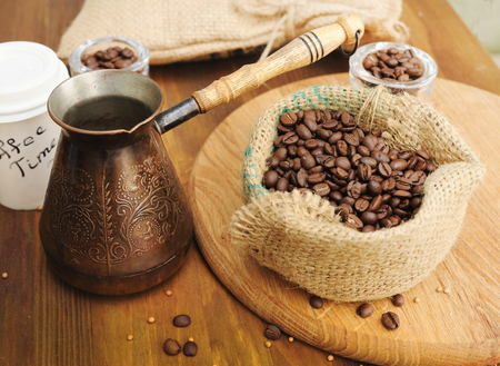 Coffee beans in burlap sack and turkish coffee pot on old wooden background