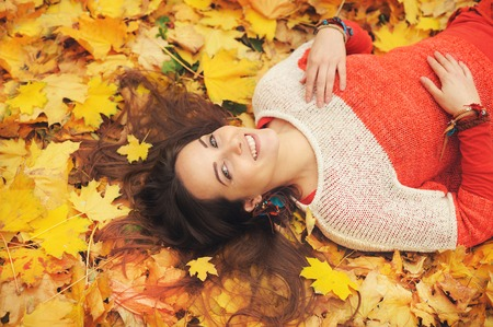 Smiling happy womanl portrait, lying in autumn leaves, dressed in fashion sweater, autumn outdoor Stock Photo