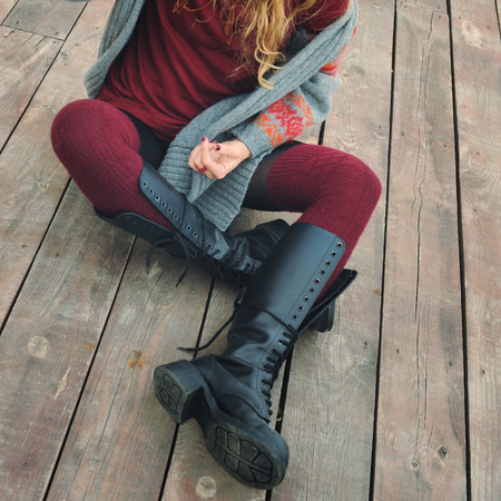 Fashion slim female legs dressed in knee high boots with shoelaces, woman sitting on a wooden planking, winter outdoor Stock Photo