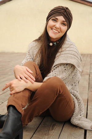 Smiling long hair woman outdoor portrait dressed in jersey turban and cardigan, autumn fashion Stock Photo