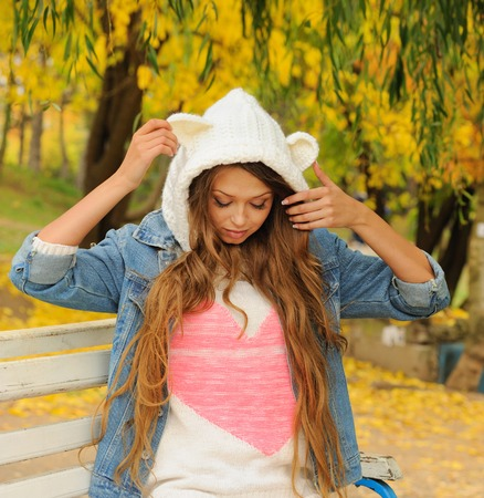 Pretty girl in a knitted bear hat posing in autumn park. Stock Photo