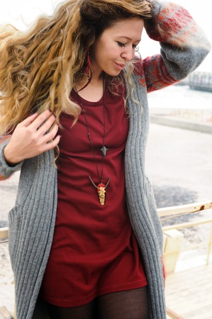 Beautiful woman portrait long hairs, short dark red dress and gray jersey. Indie style, handmade jewelry, winter outdoor