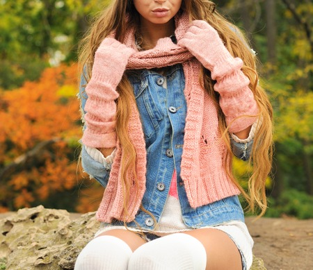 Woman posed outdoor dressed in knitted autumn outfit - warm gloves, scarf and knitted socks. No face Banco de Imagens