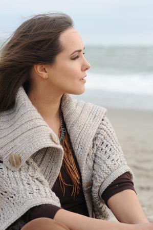 Calm woman profile portrait sitting alone on a sea beach