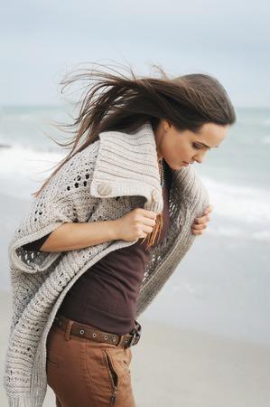 Fashion pensive woman portrait walking alone on a sea beach, autumn outdoor