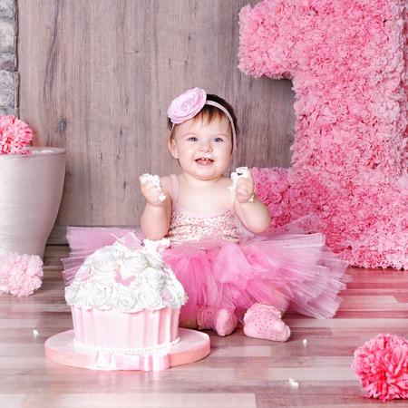 1 jaars babymeisje in roze kleding met haar eerste verjaardagscake, gelukkige verjaardagskaart