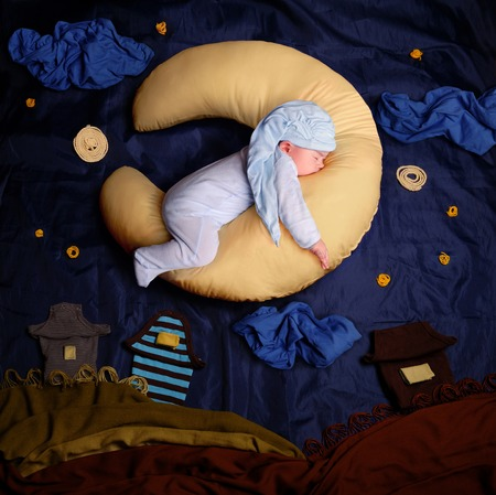 Studio portrait of infant baby boy wearing a stocking cap and blue pajamas, sleeping on a moon shaped pillow against textile decoration of a night village