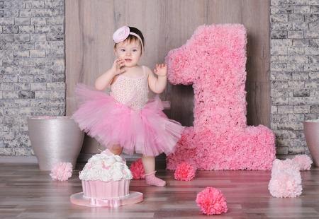 Leuk glimlachend babymeisje in roze kleding met haar eerste verjaardagscake