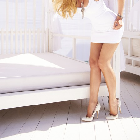 Sexy female legs in white fashion classical shoes on a heel.