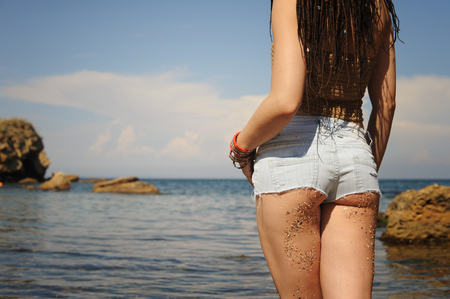 Woman buttock dressed in jeans shorts against seascape, girl with dreadlocks