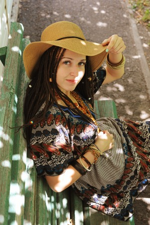 Pretty woman with dreadlocks dressed in boho style dress and hat, sitting outdoor near her home on a bench Stock Photo