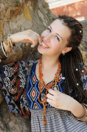 Happy smiling indie style woman with dreads, dressed in boho style ornamental dress posing outdoor Stock Photo