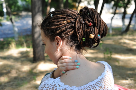 Beautiful young woman with dreadlocks hairstyle gathered in a ponytail, decorated assorted beads, outdoor, no face