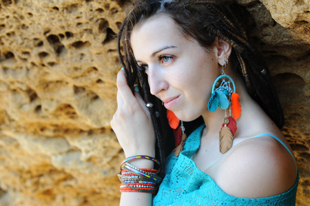 Portrait of a young smiling woman wearing dreadlocks hairstyle, dressed in blue lace dress and blue boho chic dreamcatcher earrings with leather feathers, posing against stone backdrop Standard-Bild - 109271652