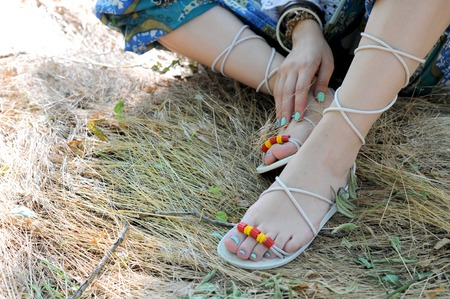Handcrafted sandals on a woman legs, close up, blue pedicures, indie style, body care concept, sunny outdoor