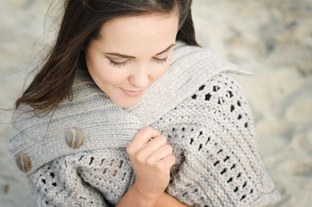 Calm woman portrait sitting on a sea beach, wrapping in knitted sweater Stock Photo