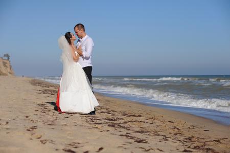 Happy bride and groom on their wedding day near the sea Banco de Imagens