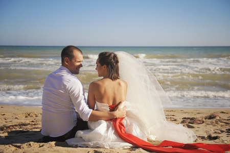 Beautiful portrait of bride with groom, wedding outdoor against seacost