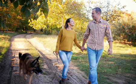 Glückliches Liebespaar, das mit Schäferhund im Park spazieren geht, Händchen hält und sich ansieht, junges Familienporträt, Freizeitkleidung, Outdoor Standard-Bild