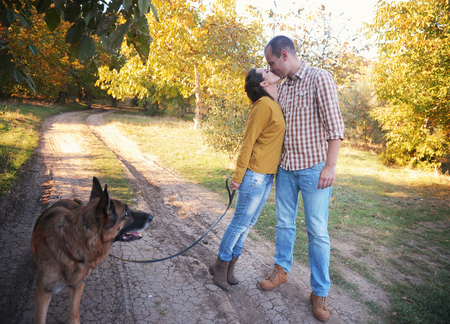 Young love couple walking in park with their german shepherd dog, have a kiss, young family portrait, casual wear, outdoor Stock Photo