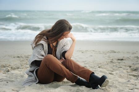 Alone sad woman sitting on a sea beach