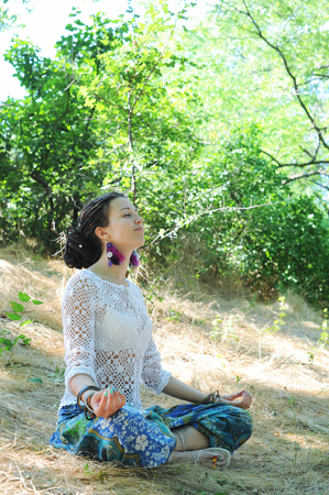 Young attractive woman meditate sitting in autumn forest, lotus pose Фото со стока