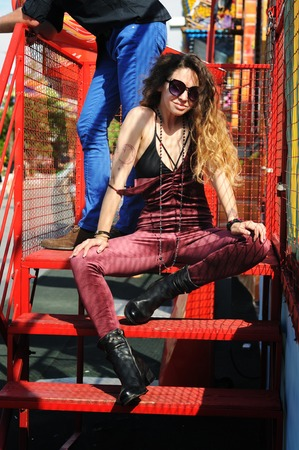 Stylish woman portrait, dressed in dark red velor overalls, looking in camera, outdoors in amusement park
