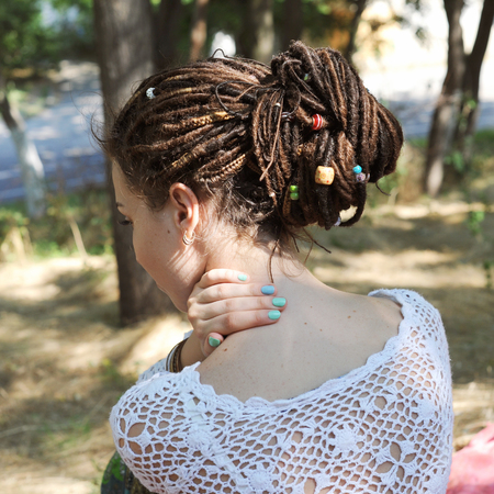 Young woman with dreadlocks hairstyle gathered in a ponytail, decorated assorted beads, outdoor, no face Stock Photo