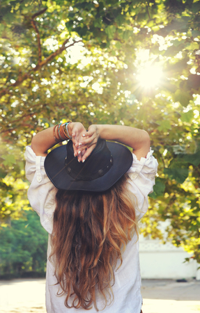 Young boho style woman enjoy sunlight in summer park, hippie, indie style, chic leather black hat, long hair, travel concept, back view, no face Stockfoto
