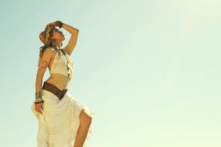 Giovane bella donna in stile boho in piedi all'aperto contro il cielo, colori sbiancati vintage, hippie, stile indie, vestito africano