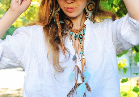 Female neck jewelery, leather necklace and earrings with feathers and natural turquoise stone, outdoor fashion photo