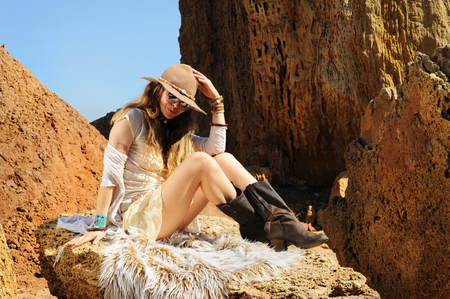 Boho style woman portrait sitting on fur, fashion hat, sunglasses and wristbands, sunny outdoor, African safari travel concept Stock Photo