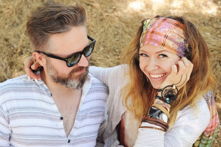 Indie style smiling couple, woman embracing man, hipster outfit, boho chic, mad in love, sunny autumn countryside against dry hay